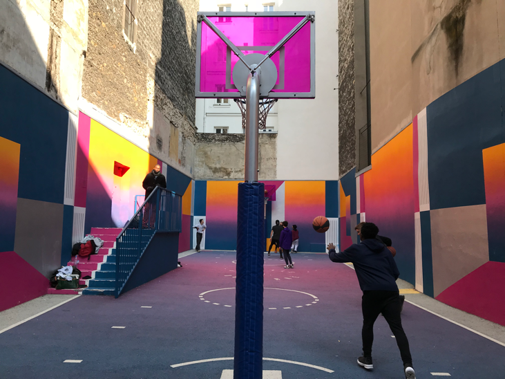 Teenagers playing a pickup game of basketball at Pigalle court in Paris, France