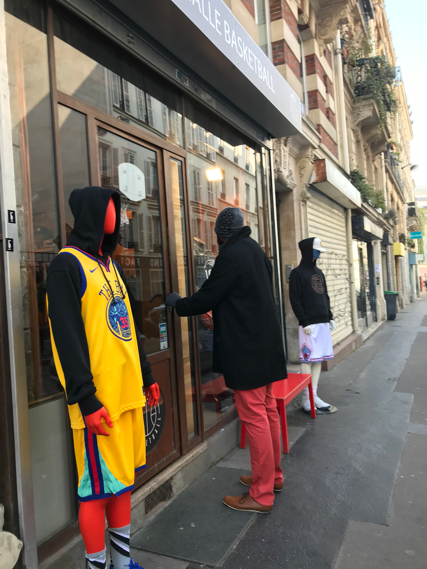 A patron enters the Pigalle Basketball shop across the street from the court