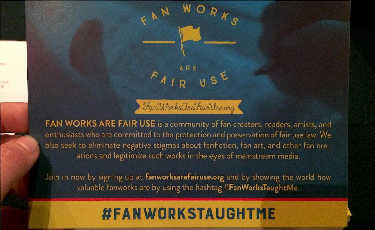 Image of a Fanworks are fair use promotional card. The text on the blue and yellow card reads: