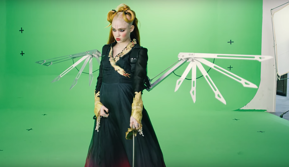 Grimes performs against a green screen for her latest single, You'll Miss Me When I'm Gone