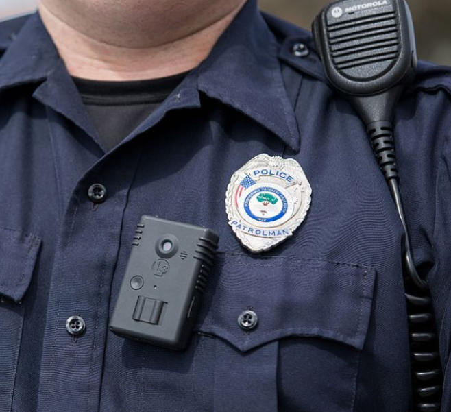 Closeup of a police officer's uniform with a badge and body camera.