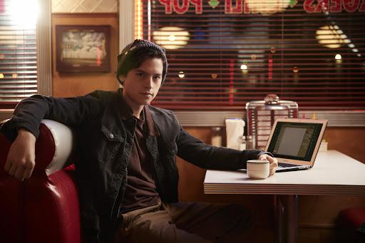 Jughead sitting in a restaurant booth with a laptop open to a blank word document