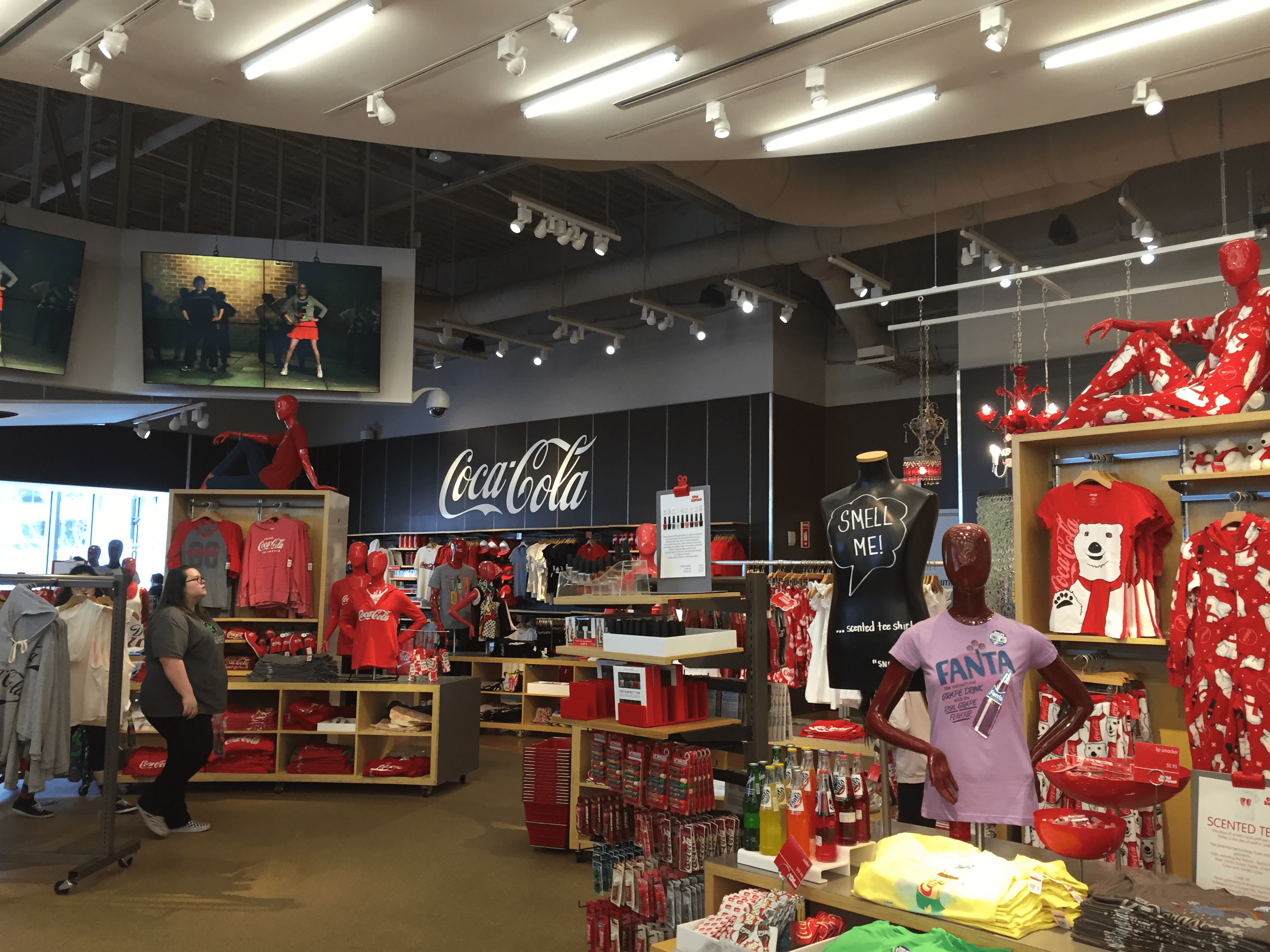 An image from the Coca-Cola store including merchandising like sweatshirts, t-shirts, pajamas, bottles of soda, and chapstick.