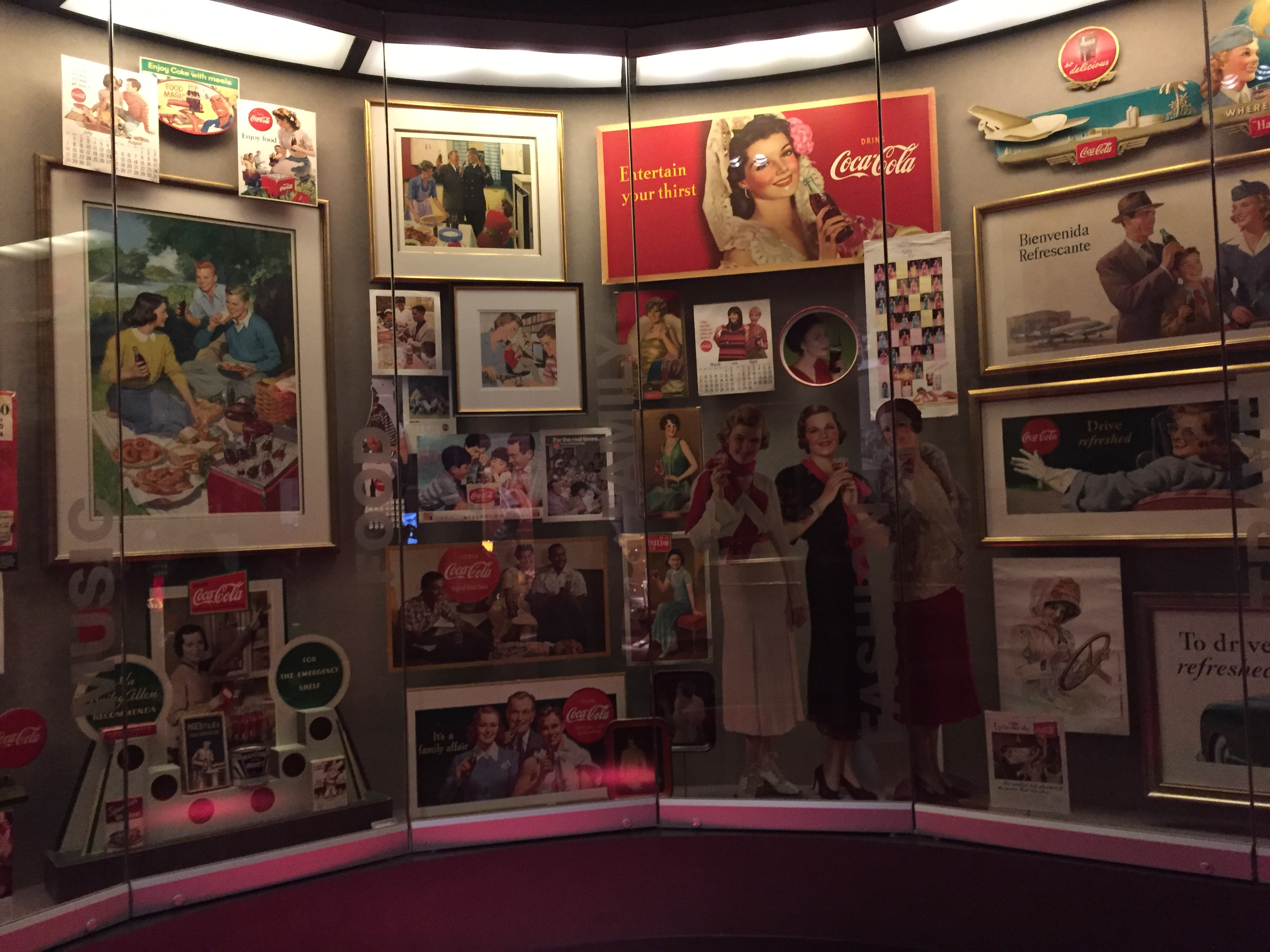 Old Coca-Cola ads and memorabilia on display behind a glass case.