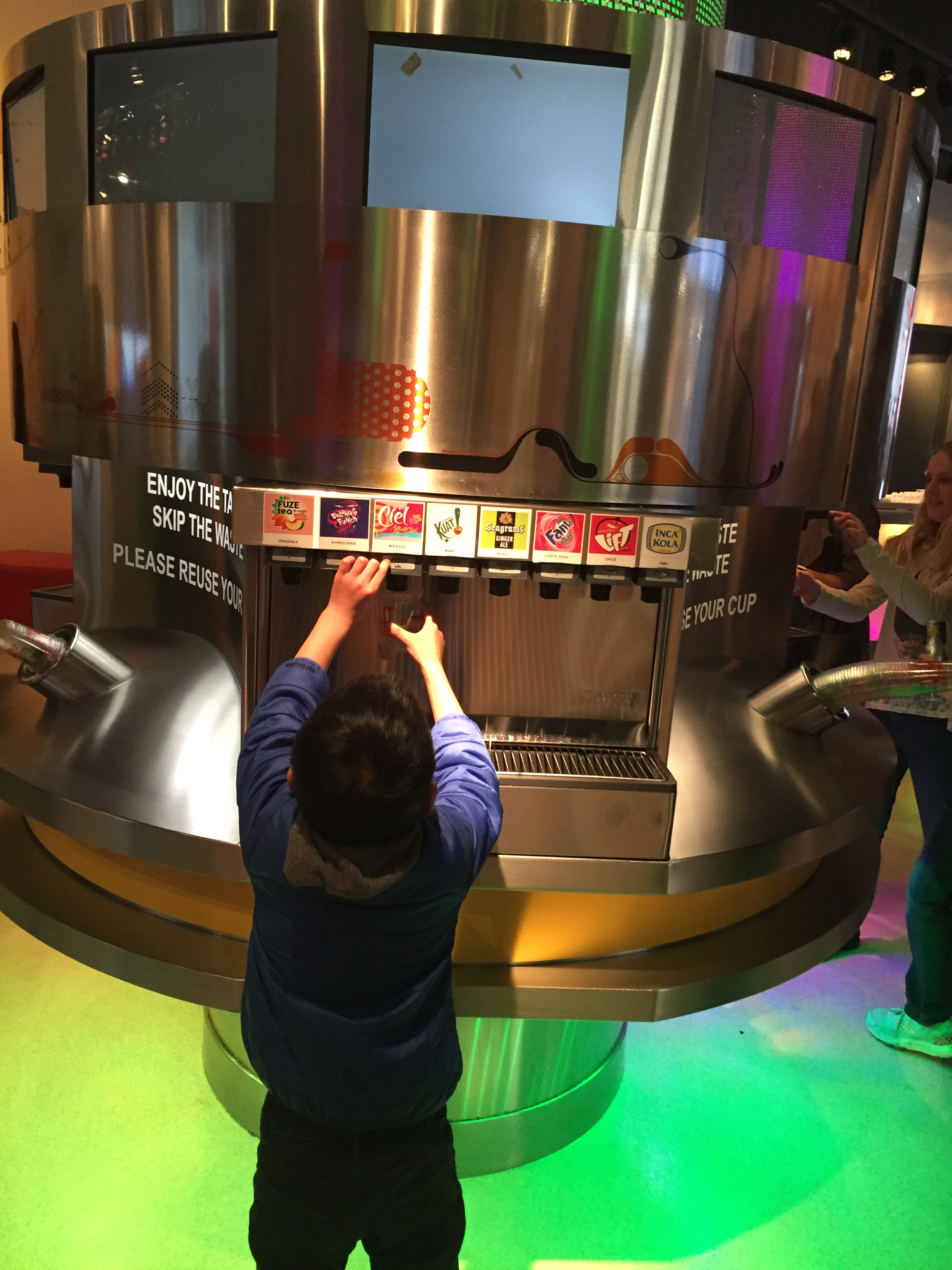 A boy reaches up to dispense a beverage called
