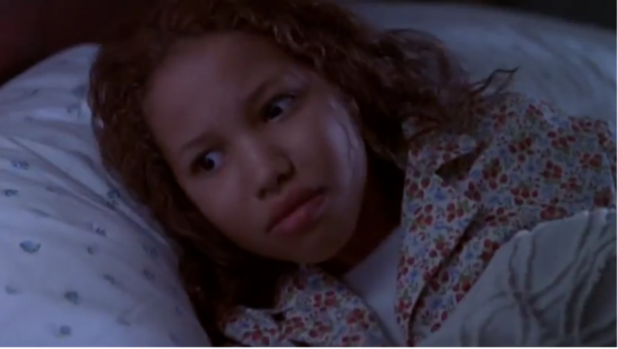 Eve (Jurnee Smollett) awakens, scared in bed