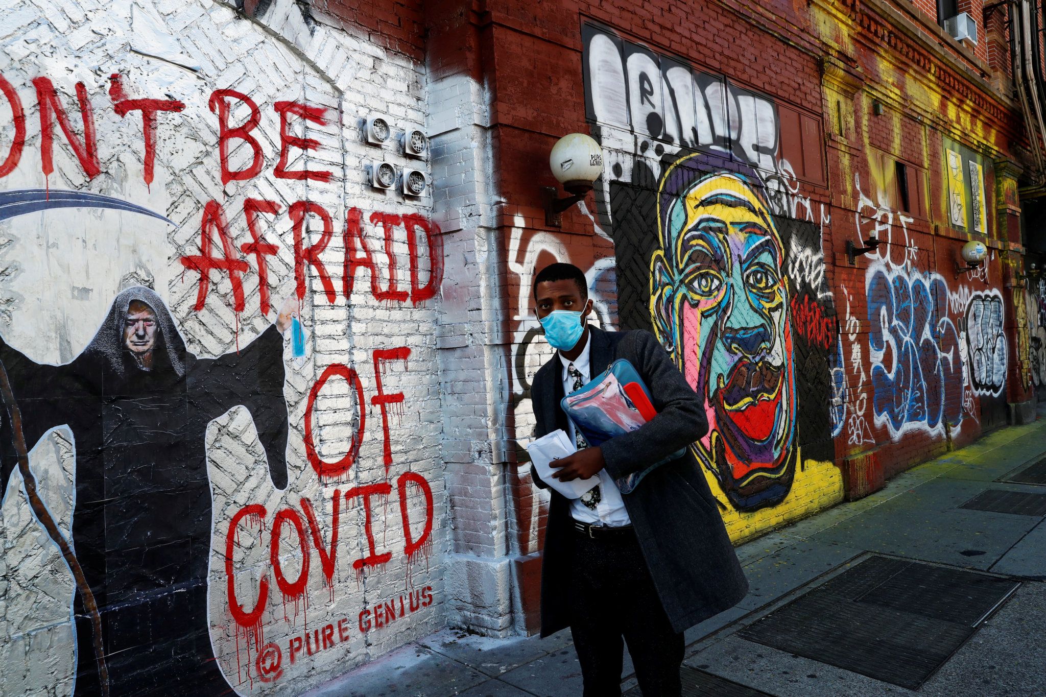 A Man walks past a Covid-19 Mural on Houston Street in NYC