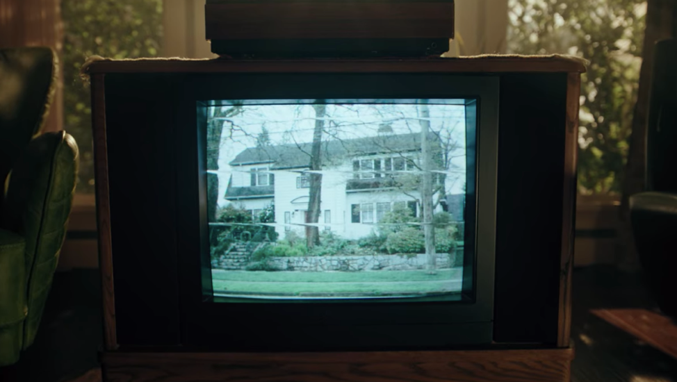 An old television set showing a suburban home