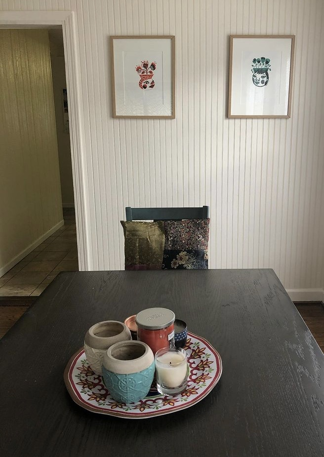 Alyx Vesey's dining room office, featuring two framed screenprints on the wall.