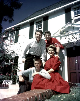 Ozzie, Harriet, David, and Rick Nelson wearing white and red posing in front of their home.