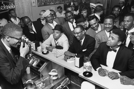 Malcolm X takes a photograph of Cassius Clay on February 25, 1964