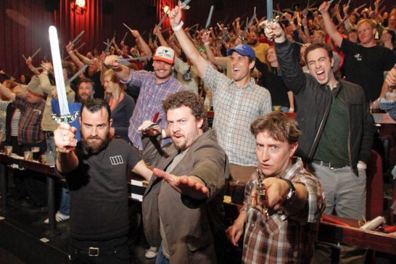 Actors Justin Theroux, Danny McBride, and director David Gordon Green stand in front of a crowd of moviegoers all holding swords at a movie event.