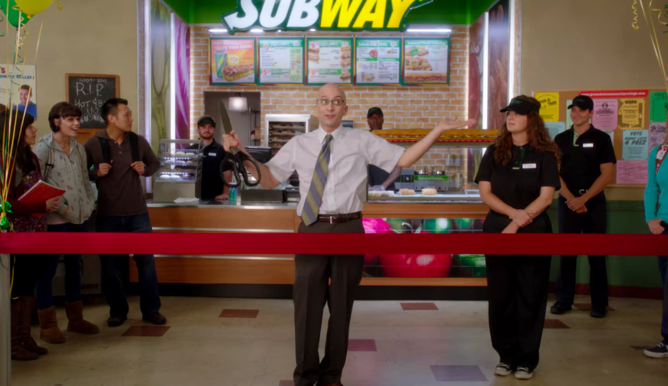 Dean Pelton from the show Community cuts the ribbon at the school's new cafeteria Subway