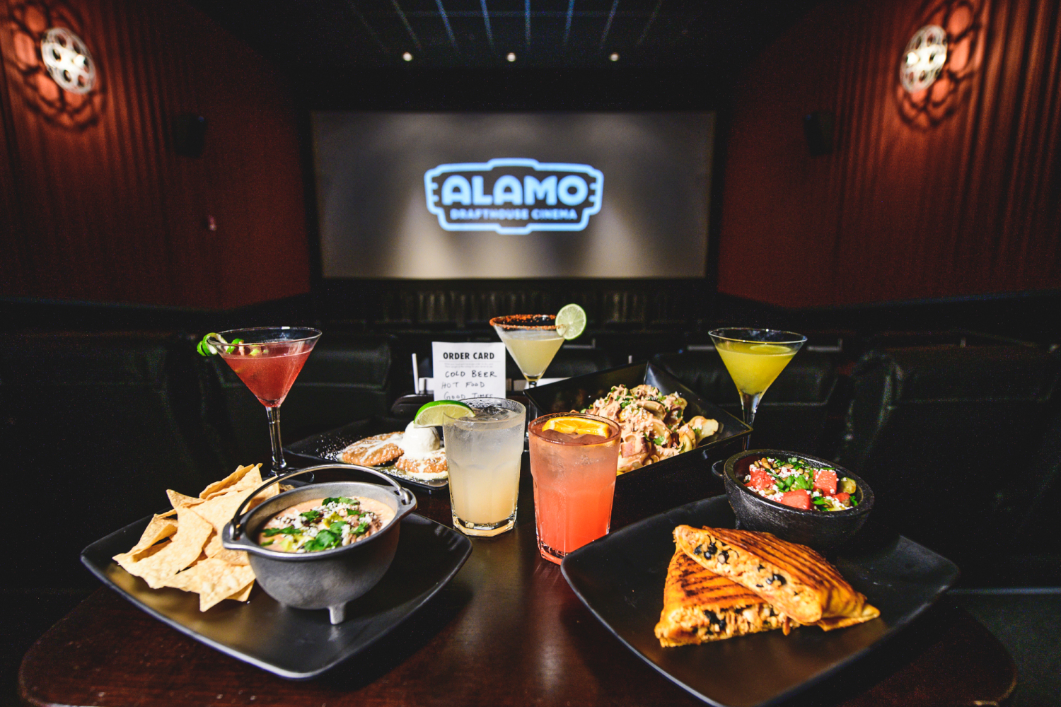 Several plates of food and alcoholic beverages sit on a table in an Alamo Drafthouse theater.