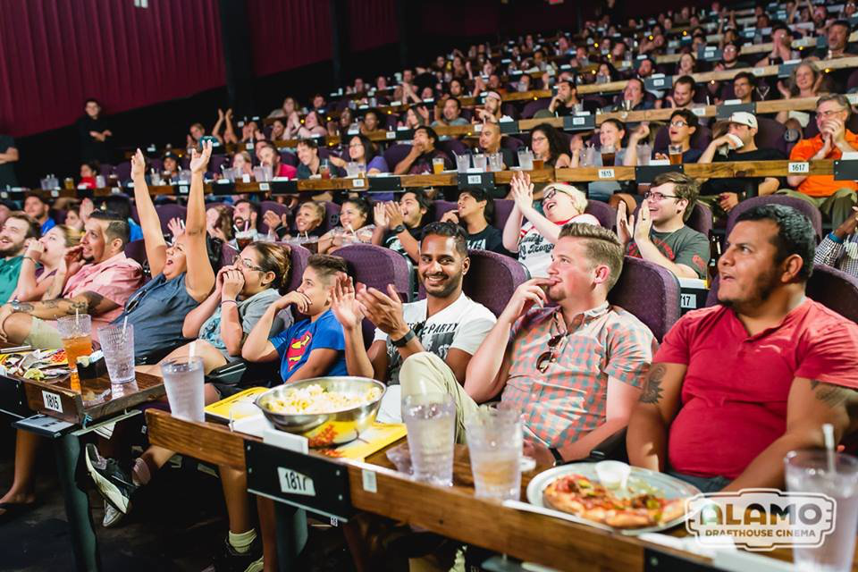 An Alamo Drafthouse theater is full of people cheering and clapping with food and beverages on tables in front of each row of seats.